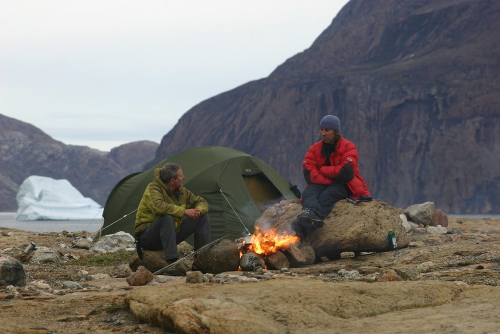sitting round a camp fire in greenland on an expedition